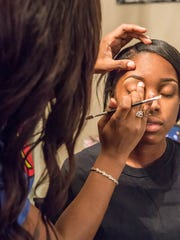 Ebony Roberson uses eye shadow on her client Canice