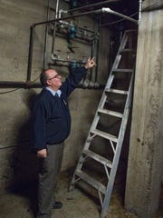 Prairieview Elementary Principal Don Hoaglin points to some of the valves in Prairieview Elementary's heating system.