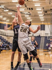 Battle Creek Central's England Bennett (22) goes for the rebound during district finals Friday evening.