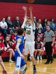 Shalom's Coby Roseman (30) take a shot while being guarded by McConnellsburg's Chance Hawbaker (22) during the Fannett-Metal Christmas Tournament. In the background, the crowd, which sits very close to the court, is visible.