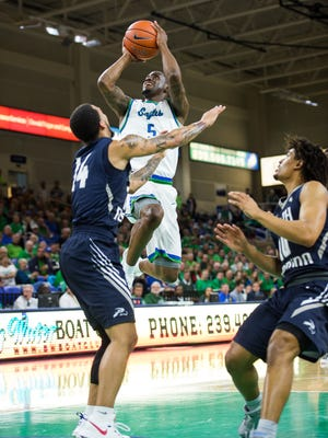Florida Gulf Coast University's Zach Johnson attempts to put up a shot against North Florida's Dallas Moore(14) during a game at Alico Arena in Fort Myers, Fla., on Monday, Jan. 30, 2017.