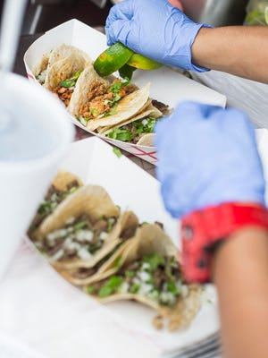 A server finishes off a customers tacos with a few lime wedges while outside of Maria's Restaurant during a Taco Tuesday event in Bonita Springs.
