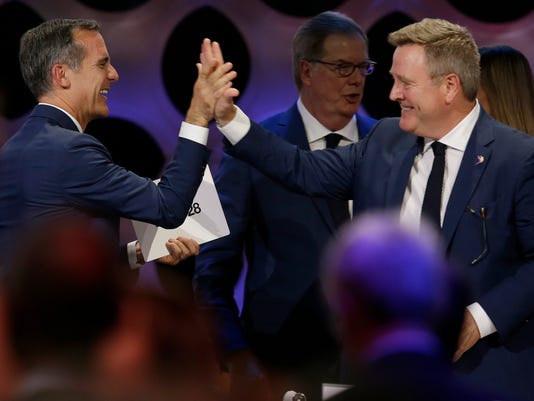 Los Angeles Mayor Eric Garrett, left, celebrates with United States Olympic Committee Executive Officer Scott Blackmun at the end of the IOC session in Lima, Peru, Wednesday, Sept. 13, 2017. The International Olympic Committee voted to ratify Los Angeles as the host city of the 2028 Olympic and Paralympic Games and Paris as the host city of the 2024 Games. (AP Photo/Martin Mejia)