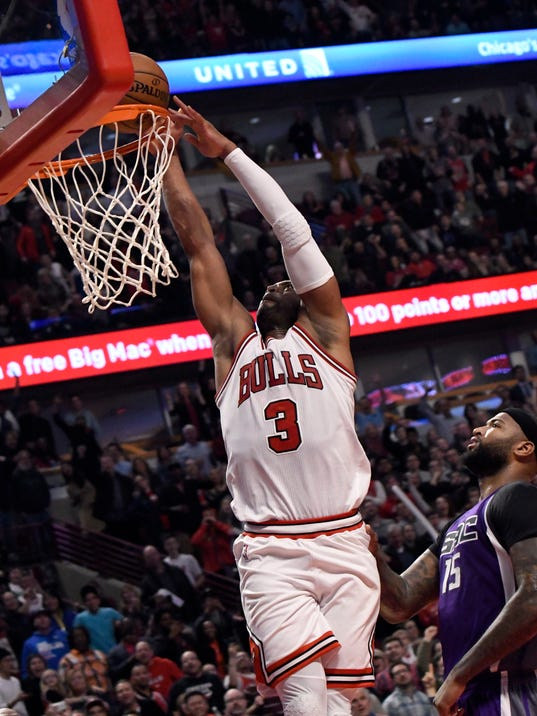 Chicago Bulls guard Dwyane Wade (3) is fouled going up for a dunk by Sacramento Kings forward DeMarcus Cousins (15) during the second half of an NBA basketball game in Chicago, Saturday, Jan. 21, 2017. (AP Photo/David Banks)