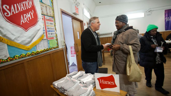 In this 2013 photo from Giving Tuesday, clothing brand Hanes and Mark Horvath, left, an advocate for the homeless, teamed up to donate half a million socks to The Salvation Army and other charities over the course of a month.