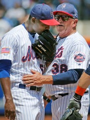New York Mets pitching coach Dan Warthen (38) talks to starting pitcher Rafael Montero, left, during the second inning of a baseball game against the Philadelphia Phillies, Sunday, July 2, 2017, in New York.