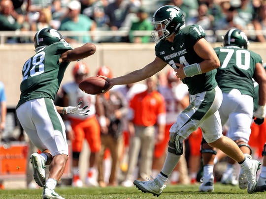 Sep 2, 2017; East Lansing, MI, USA; Michigan State Spartans quarterback Brian Lewerke (14) hands the ball off to Michigan State Spartans running back Madre London (28) during the second half of a game at Spartan Stadium. Mandatory Credit: Mike Carter-USA TODAY Sports