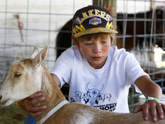 Jayde Murphy, 12, of Cut Bank pets a goat at the Marias