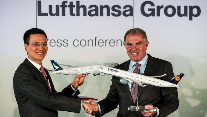 Ivan Chu (left), CEO of Cathay Pacific Airways and Carsten Spohr (right), CEO of Deutsche Lufthansa, shake hands during a press conference at the Lufthansa Aviation Center in Frankfurt March 27, 2017.