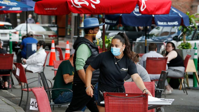 A waitress seats customers at a restaurant with outdoor dining on a section of street closed to traffic to promote social distancing, Friday, July 17, 2020, in Somerville, Mass.