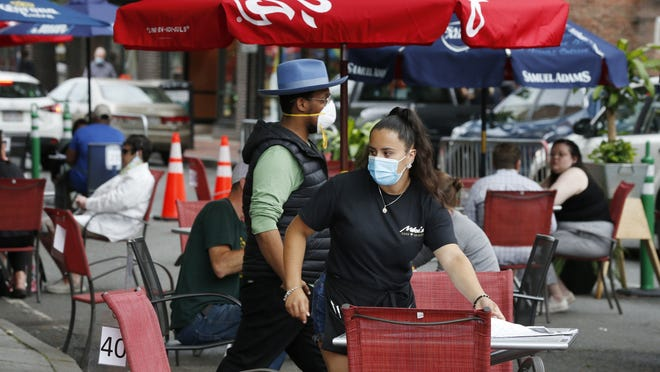 FILE - A waitress seats customers at a restaurant with outdoor dining on a section of street closed to traffic to promote social distancing, Friday, July 17, 2020, in Somerville, Mass.