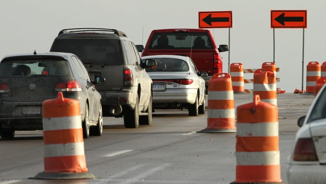 Motorists follow traffic-shift signs as the closure of southbound lanes on the Latson Road overpass above Interstate 96 forces a slowdown in the area.