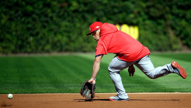 St. Louis Cardinals' Kolten Wong tries to catch a ball during an NLDS baseball practice on Oct. 11 in Chicago. The Cardinals will face the Chicago Cubs in Game 3 of the National League Division Series on Oct. 12.