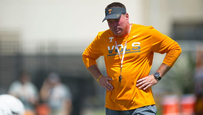 Coach Butch Jones watches as Tennessee football players warm up during a preseason practice on Aug. 16, 2016.