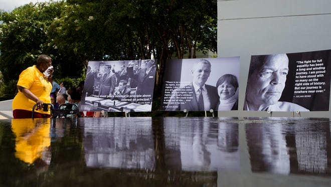 Elaine Harrington, civil rights worker, looks at photographs of Julian Bond during a memorial to honor civil rights leader Julian Bond held by the Southern Poverty Law Center on Saturday, Aug. 22, 2015 in Montgomery, Ala.