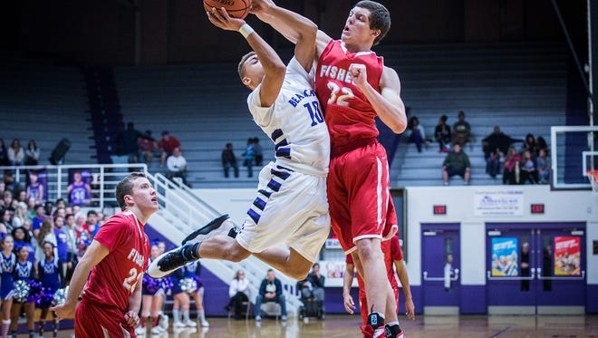Central's Jamel Barnes takes a foul while going up for a shot against Fishers' defense during their game at the Muncie Fieldhouse Tuesday, Dec. 22, 2015.