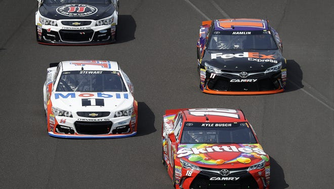 Sprint Cup Series driver Kyle Busch (18) leads Tony Stewart (14) and  Denny Hamlin (11) during the Brickyard 400 Sunday, July 24, 2016, afternoon at the Indianapolis Motor Speedway.