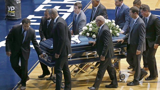Pallbearers escort the casket of former Butler basketball star Joel Cornette off the court at Hinkle Fieldhouse on Monday after a celebration of life.