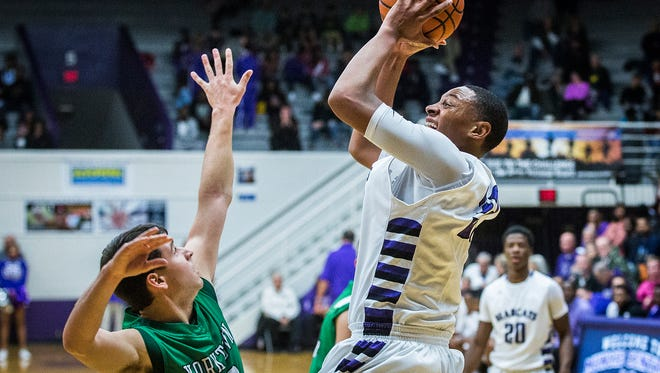 Central's Christian Wells shoots past Yorktown's defense during their game at the Muncie Fieldhouse Saturday, Nov. 26, 2016. Central defeated Yorktown 77-40.