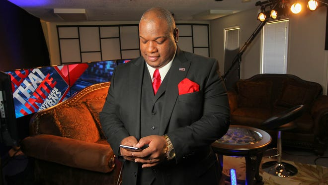 Rev. Mark Burns of Colors That Unite checks his phone before an interview in his studio in Easley on May 17.