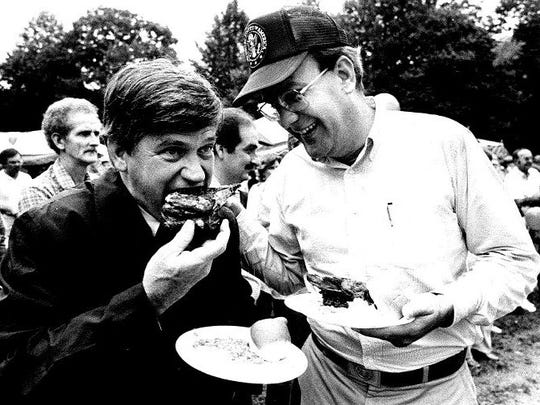 Then-Gov. Jim Martin, left, bites into some fried chicken at a political event in the 1980s while Bill Hendon smiles at right.