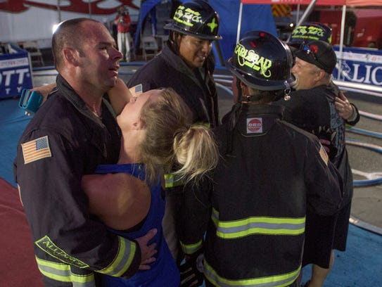 Carlsbad firefighter Casey Collins is hugged by his