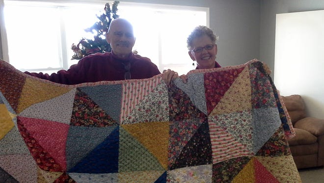 Jerry and Gail Hillgard display a handmade quilt donated to Christmas Wish by the Hill 'N Hollow Quilt Guild. The quilt will be auctioned at the Christmas Wish Pie Auction set for 2-6 p.m. Nov. 22 at Alley-White American Legion Post 52, 717 Market St.