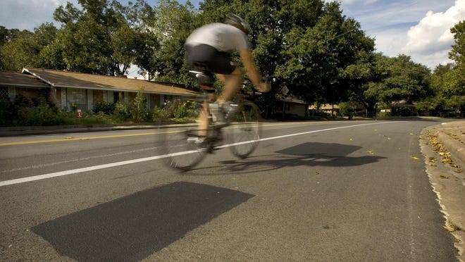 A cyclist rides along Shoal Creek Boulevard.