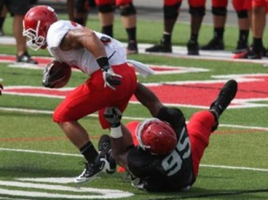 Rutgers nose guard Kenneth Kirksey drags down a ball-carrier during training camp in 2013. He is back on the field after a triceps injury.