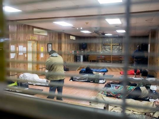 Men make their beds of mats and blankets inside the chapel at the WNC Rescue Mission on Patton Avenue in Asheville Tuesday night. The mission sees an influx of people during the winter months and doesn't refuse shelter to anyone arriving inside by 6:00 p.m. When they use up all the mats available, the mission provides cots.
