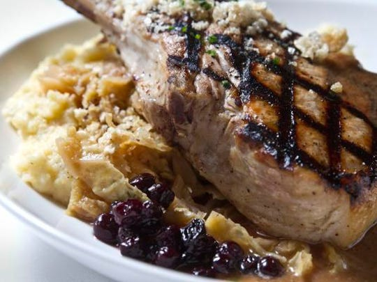 Cheddar garlic grits and apple and bacon braised cabbage with bourbon pork chop and pickled huckleberries.