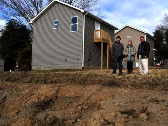 From left to right, Ethan Summers and Penny Sampson of Homeward Bound stand with Kirk Booth, an affordable-housing developer next to broken ground for new housing units next to some new affordable units for rent at 9 Marigold St. in Asheville on Friday.
