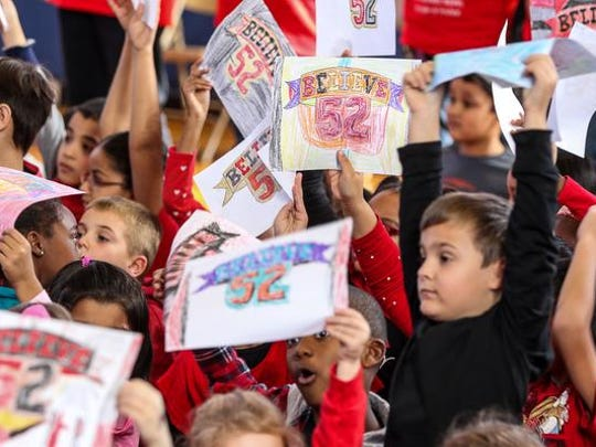 "Children hold up signs during the assembly as Eric LeGrand visits Knollwood Elementary School in Piscataway for ""Eric Legrand Day"" on November 13, 2015."