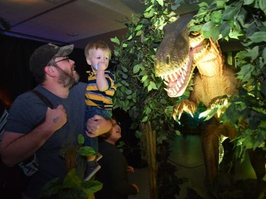 "John Long and his sons Braxson Wolf, 18 months, and Jameson Long, 8, play with an animatronic dinosaur which is part of the ""Discover The Dinosaurs"" exhibit at the Alexandria Riverfront Center. The exhibit continues from 10 a.m. to 7 p.m. Sunday."