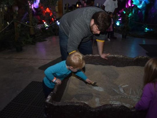 "Josh Wiggins and son Corbett Wiggins play in the dino dig that is part of the ""Discover The Dinosaurs"" exhibit at the Alexandria Riverfront Center. The exhibit continues from 10 a.m. to 7 p.m. Sunday."