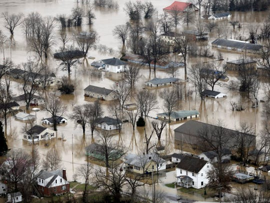 In this aerial photo, homes and businesses are surrounded