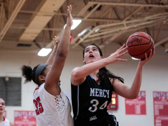 Butler's Janna Lewis (35) attempts to block a shot from Mercy's Danielle Feldkamp (34) during the first half of play, Friday, January 15, 2016, at Butler Tradition High School in Louisville, Ky.