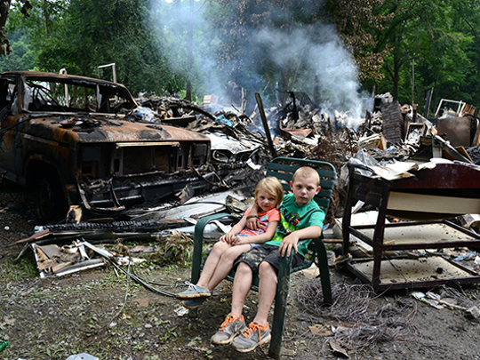 Hayleigh Scott and her brother Remington sit in front of what remains of their home in White Sulphur Springs, W.Va. Their family's house was flooded, then caught fire. Their parents survived, but their grandmother died in the flooding.