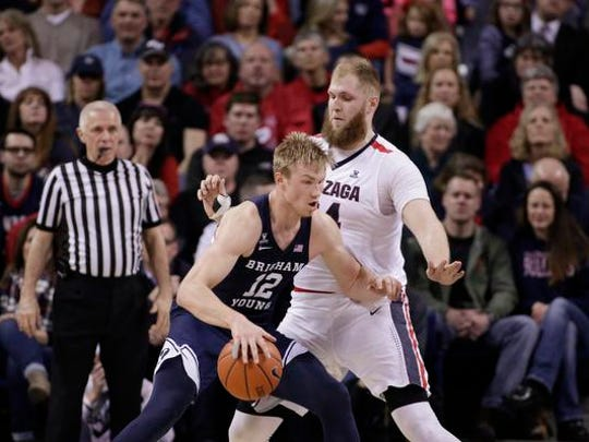 BYU forward Eric Mika (12) posts up on Gonzaga center Przemek Karnowski during the first half of an NCAA college basketball game in Spokane, Wash., Saturday, Feb. 25, 2017. The West Coast Conference begins tournament play on Friday, March 3