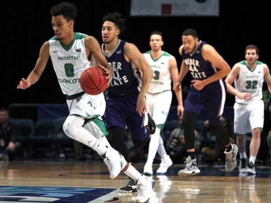 North Dakota guard Geno Crandall (0) drives the ball up court against Weber State during the first half an NCAA college basketball game Saturday  in the finals of the Big Sky tournament in Reno.