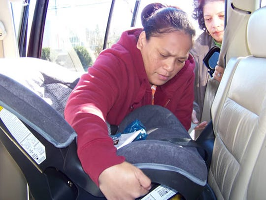 Kaye Brownlee (right), certified child passenger safety technician, instructs a parent on correct car seat installation at the Henderson County Health Department.