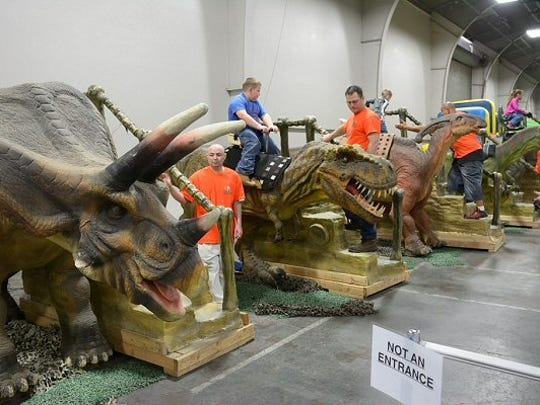 Children ride the dinos at the Jurssic World event that is making its first ever stop in Evansville this weekend.
