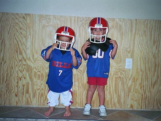 Joe Lang, left, and Zach Lang, right, pose as youngsters in football gear.
