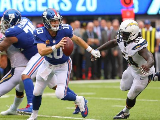 New York Giants quarterback Eli Manning (10) runs with