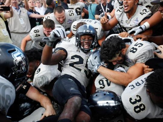 Dec 2, 2017; Orlando, FL, USA; UCF Knights defensive back Kyle Gibson (25) celebrates with teammates after beating the Memphis Tigers in double overtime at Spectrum Stadium. Mandatory Credit: Matt Stamey-USA TODAY Sports