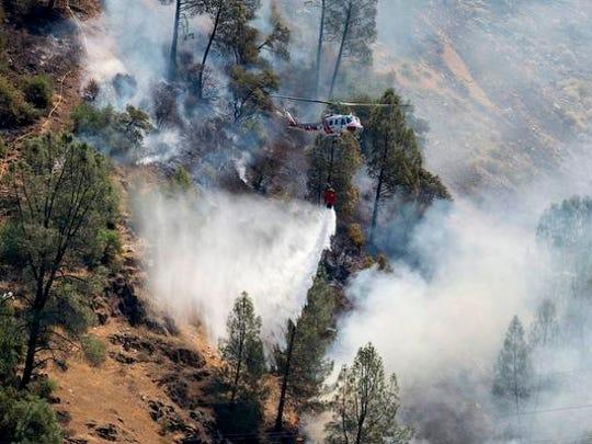 Crews battle the Ferguson Fire along steep terrain behind the Redbud Lodge along Highway 140 near El Portal in Mariposa County, Calif., on Saturday, July 14, 2018.  (Andrew Kuhn /The Merced Sun-Star via AP)