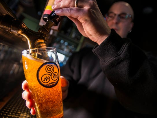 General Manager Todd Balcom pulls a pale ale from Goodwater Brewery from the extensive tap options at McGillicudy's at Maple Tree Place in Williston in February 2017.