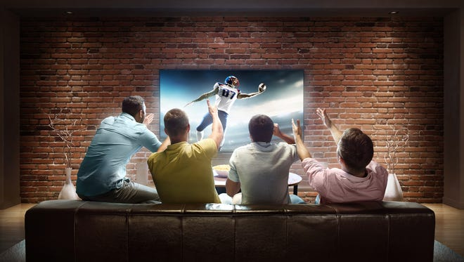 :biggrin:A group of young male friends are cheering while watching American football game at home. They are sitting on a sofa in the modern living room faced to a big TV set on the front wall.