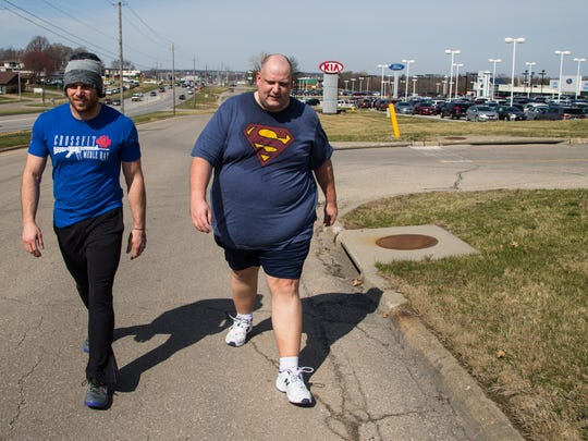 Daniel Finney walks with coach Nate Yoho outside CrossFit
