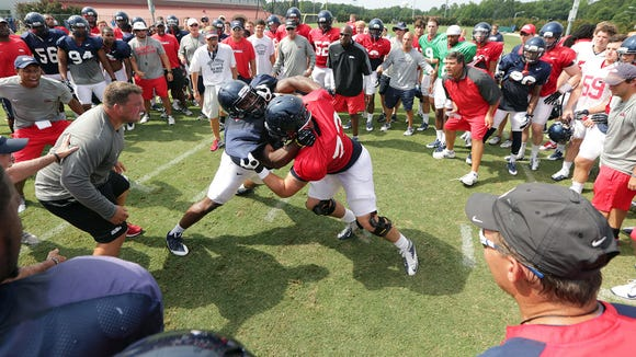 Ole Miss defensive end Fadol Brown, left, goes through a drill in August 2013. He sat out the season because of NCAA transfer rules.